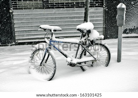 biking covered with snow in the winter blizzard in the parking lot - stock photo