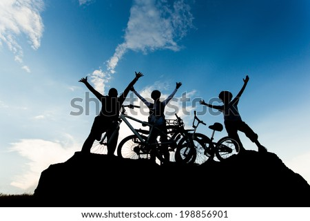 Biking family at sunset sky background. Active healthy outdoor lifestyle concept - stock photo