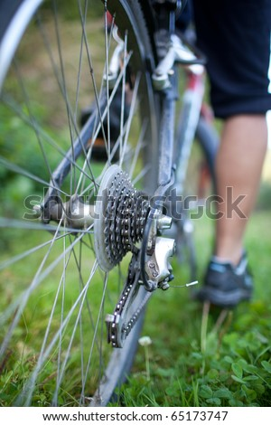 biking - rear wheel of a young woman's mountain bike on a green mountain path (shallow DOF - selective focus) - stock photo