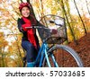 Biking, Woman on bike in autumn forest. Beautiful mixed asian / caucasian model. - stock photo