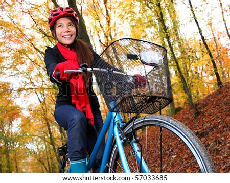 Biking, Woman on bike in autumn forest. Beautiful mixed asian / caucasian model. - stock photo