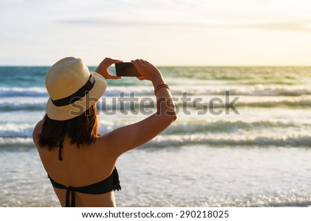 Bikini asia woman tourist taking photo on sea beach with mobile smart phone camera at sunset