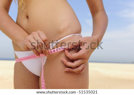 Bikini body:: Young woman wearing bikini measuring her hips on the beach - stock photo