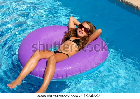 bikini children girl with sunglasses relaxed on purple inflatable pool ring