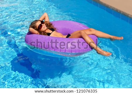 bikini children girl with sunglasses relaxed on purple inflatable pool ring - stock photo