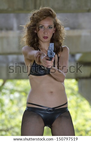 Bikini clad woman in gangster style aiming with a handgun - outdoor - stock photo