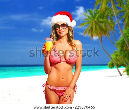 Bikini, fitness model with Santa Hat, sunglasses and cocktail having tropical vacation on Maldives. Happy beautiful woman with suntan, smiling. Christmas card. - stock photo
