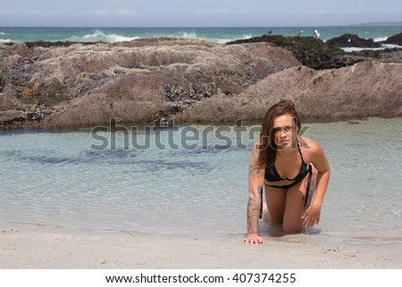 Bikini model crawling out of the sea - stock photo