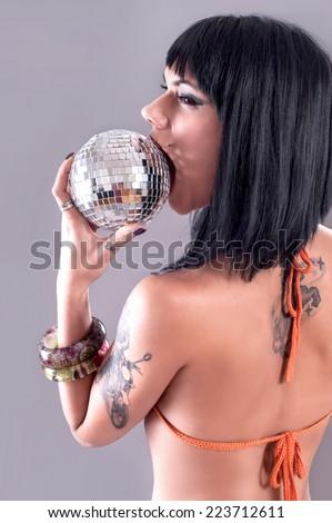 Bikini Sexy Model. Sexy brunette in a colorful bikini with disco ball - stock photo
