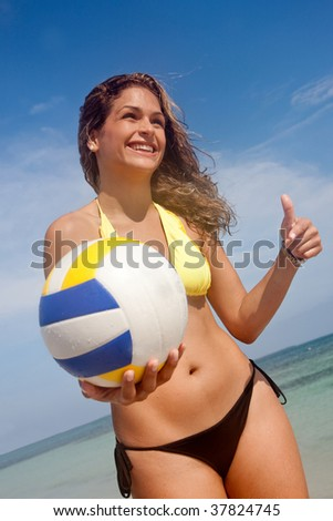Bikini woman at the beach with a volleyball - stock photo