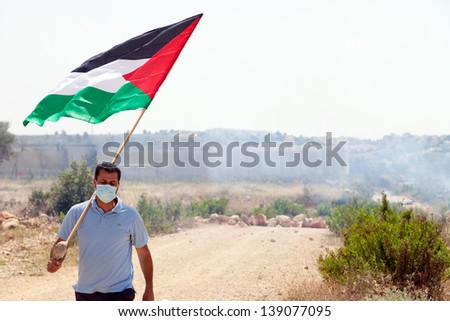 BIL'IN, PALESTINE - MAY 17: A Palestinian protester holding the Palestine flag walking away from the wall of separation at a protest against the Israeli occupation on May 17, 2013 in Bil'in, Palestine - stock photo