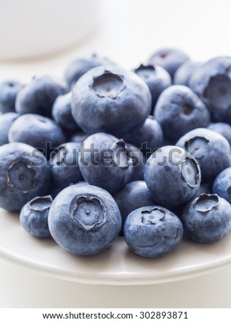 Bilberries (whortleberries) on a small plate, close up.