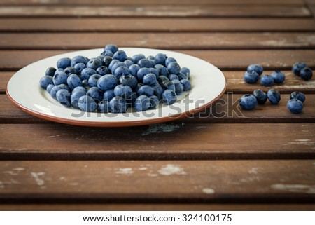 Bilberry on a plate on a wooden table