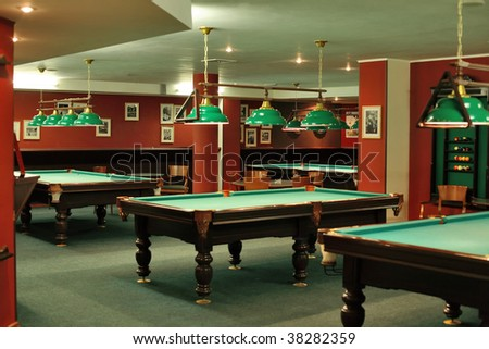 Biliard room with four tables and pictures on the red walls - stock photo