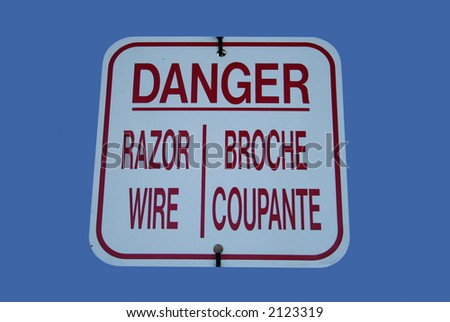 Bilingual danger razor wire sign