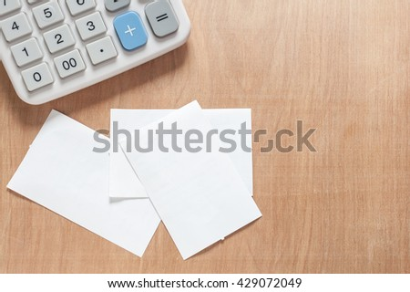 Bill and calculator on wooden, Macro paper bill and calculator on wooden texture, Bill for income and expenditure with copy space  - stock photo