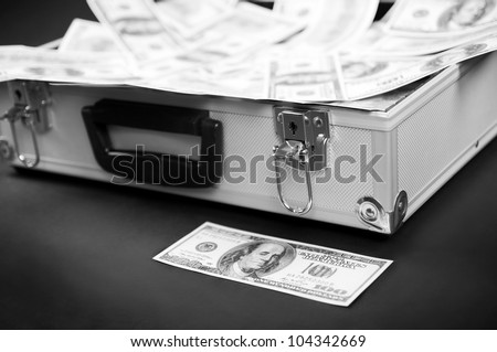 bill before the metal suitcase with a bunch of money - stock photo