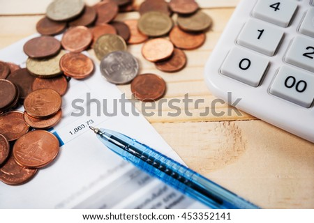 Bill with coins and pen and calculator on table, Money for income and expenditure saving for dream - stock photo