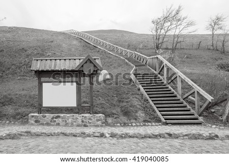 Billboard and wooden stairs, hill and rocky road