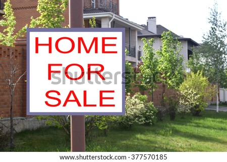 "Billboard ""House for sale"" on the background of cottages"