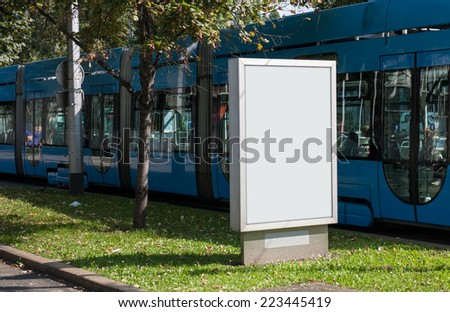 Billboard on city street with tram in background - stock photo