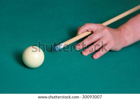 Billiard ball and hand on green table - stock photo