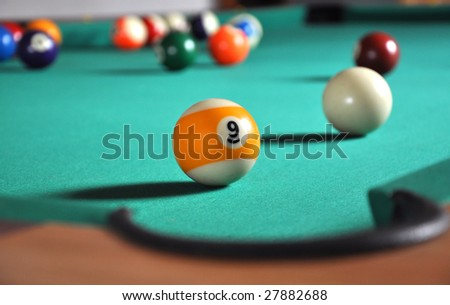 Billiard ball near hole, a lot of balls in blurry background