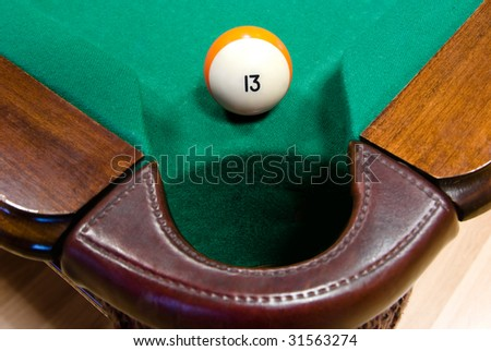 billiard ball number thirteen by corner pocket - stock photo