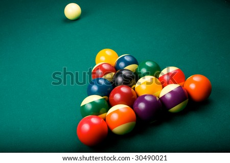 Billiard balls are racked in a triangle, waiting to be broken by the cue ball. Shallow depth of field. - stock photo
