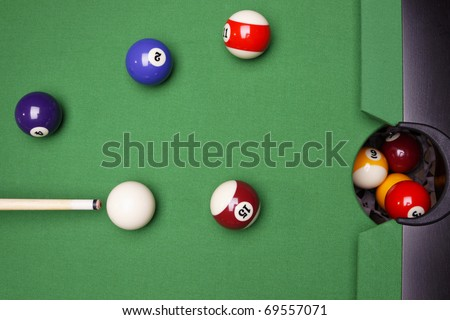 Billiard balls composition on green pool table - stock photo