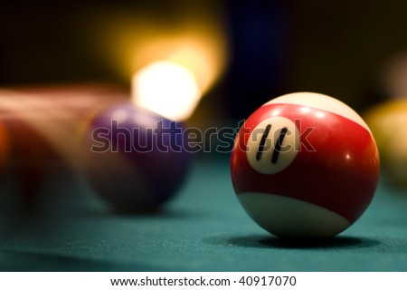 Billiard balls in motion on a pool table - stock photo