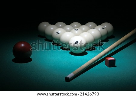 Billiard. Balls pyramid with number 8 ball of center. Selective focus on a 8ball. Floodlit scene. - stock photo