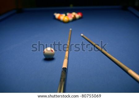 Billiard blue table with balsl and cues in beginning position. - stock photo