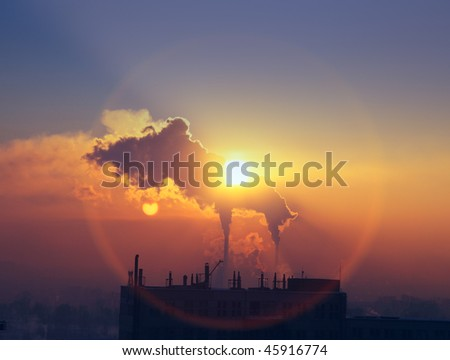 billowing smoke into the atmosphere at sunset - stock photo