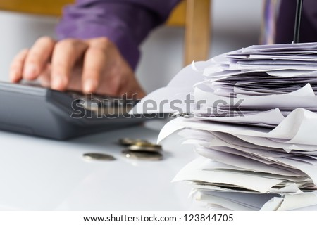 Bills in paper nail with hand calculating - stock photo