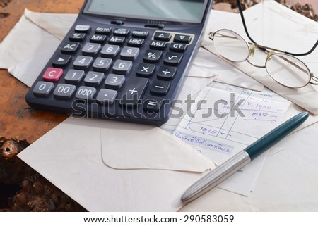 Bills on Table with Calculator - stock photo
