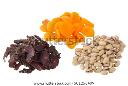 Biltong, dried apricot and pistaccio nuts on a white background. Biltong is a South African cured meat delicacy.