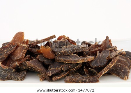 Biltong is a healthy low fat, high protein cured dry meat suitable for dieting using sun dried methods of food preservation, copy space, on white, macro, - stock photo