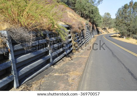 Bin-type retaining wall protects mountain road from landslides - stock photo