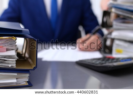 Binders with papers are waiting to be processed with businessman and secretary back in blur. Accounting planning budget, audit, insurance  and business concept - stock photo