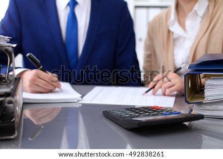 Binders with papers are waiting to be processed with businessman and secretary back in blur. Internal Revenue Service inspector checking financial document.