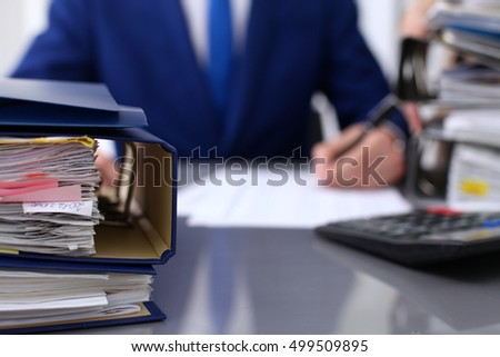 Binders with papers are waiting to be processed with businessman and secretary back in blur. Accounting planning budget, audit, insurance  and business concept