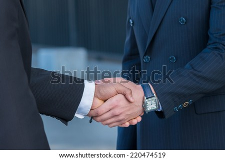 Binding agreement with a handshake. Two businessmen shaking hands on the street - stock photo