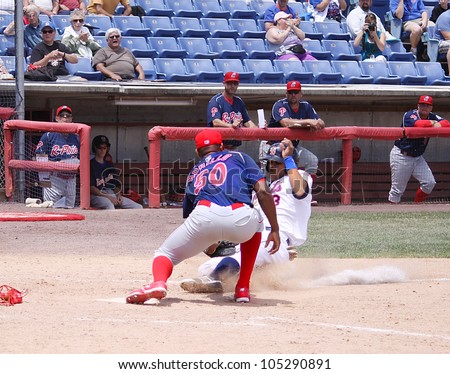 BINGHAMTON, NY - JUNE 14: Reading Phillies' Juan Morillo tags out the runner at home plate during a game against the  Binghamton Mets at NYSEG Stadium on June 14, 2012 in Binghamton, NY - stock photo