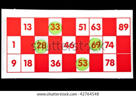 Bingo card with four numbers covered up by green counters - stock photo