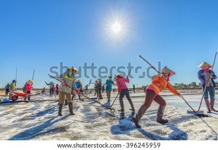 Binh Thuan, Vietnam - January 22nd, 2016: Close group of fishermen are raking salt in the sun rhythm Early harvest promises a lot of salt in the coastal countryside Binh Thuan, Vietnam - stock photo
