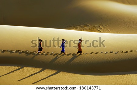 BINH THUAN, VIETNAM, May, 11: Cham people in Phan Thiet provice go throught the sand dunes daily after their bussiness, on May, 11, 2013 in Mui Ne, Binh Thuan, Vietnam.  - stock photo