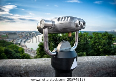Binocular next to the waterside promenade i looking out to the city and river - stock photo
