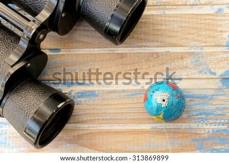 Binoculars and globe  - stock photo