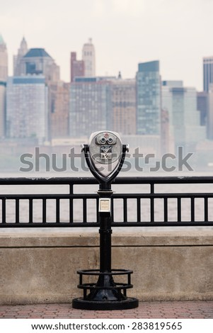 Binoculars and New York City Manhattan skyline in the background over Hudson River viewed from New Jersey Liberty State Park at daytime. - stock photo